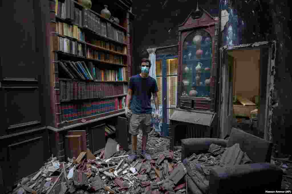aid Al Assaad, 24, poses for a photograph inside his grandfather's destroyed villa after Tuesday's explosion in the seaport of Beirut, Lebanon, Thursday, Aug. 6, 2020.