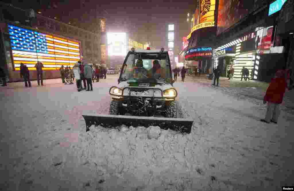 A plow pushes snow in New York's Times Square. The governors of New York and New Jersey declared a state of emergency and urged residents to stay indoors as a major storm struck on January 2.