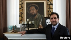 Ахмад Зиа Масуд, возможный кандидат в президенты Афганистана, фотографируется на фоне портрета своего брата - таджикского командира Ахмад Шаха Масуда.