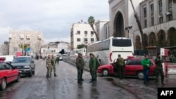 Syrian security forces cordon off the area following a deadly suicide bombing at a Damascus courthouse on March 15.
