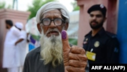 An elderly Pakistani man shows his inked thump outside a polling station after casting his vote in national elections in Lahore on July 25.