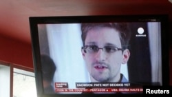 Russia -- A television screen shows former US spy agency contractor Edward Snowden during a news bulletin at a cafe at Moscow's Sheremetyevo airport, July 24, 2013