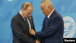 Russia -- Uzbek President Islam Karimov (R) adjusts the suit of Russian President Vladimir Putin during the Shanghai Cooperation Organization (SCO) summit in Ufa, July 10, 2015