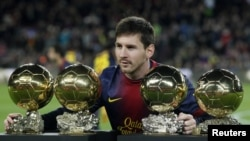 Lionel Messi 2009, 2010, 2011 va 2012 yillarda olgan Oltin to'plari bilan. Oltin to'p FIFA tarafidan dunyoning eng yaxshi futbolchisiga beriladi.