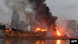 A ship is pictured engulfed in flames at the port of Beirut following a massive explosion that hit the heart of the Lebanese capital on August 4, 2020
