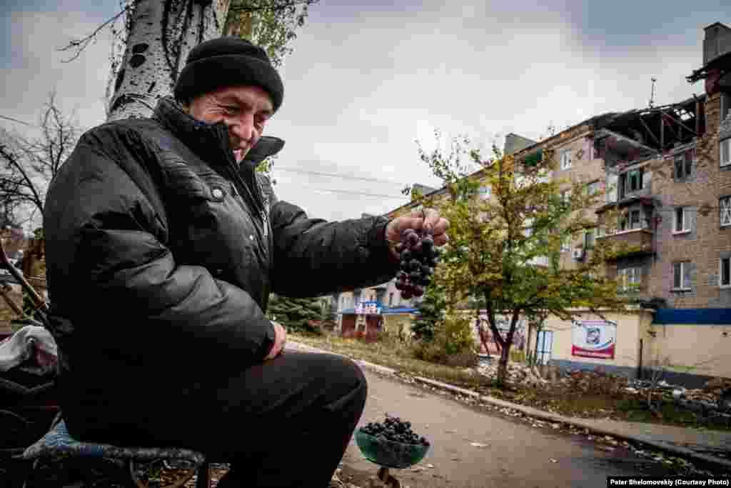 Өз бағында өсірген жүзімді сатып отырған Горловка тұрғыны Николай. Тұрғындарелдімекендегі үйлеріне орала бастады, бірақ жұмыс табу өте қиын. Қазан, 2014 жыл.