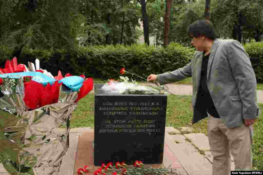 """Оппозициялық """"Ашық алаң"""" газетінің редакторы Жанболат Мамай саяси қуғын-сүргін құрбандарына арнап гүл қойып жатыр. Алматы, 31 мамыр 2014 жыл."""