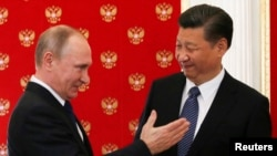 Russian President Vladimir Putin (left) greets Chinese President Xi Jinping at a meeting in the Kremlin in Moscow on July 3.
