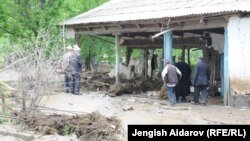 Residents of the village of Kulundu in the Batken region inspect a building damaged in the flooding on April 26.