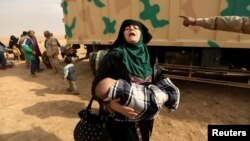 A woman fleeing fighting between Islamic State militants and Iraqi forces in eastern Mosul reacts as she heads to safer territory on November 8.