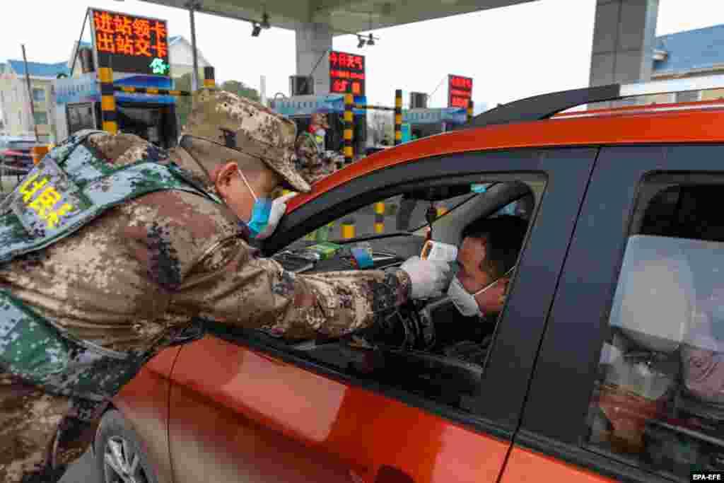 Милиция Ухань қаласының ақылы шоссесіне кіреберіс жерде жолаушылардың дене қызуын тексеріп жатыр. 23 қаңтар 2020 жыл.