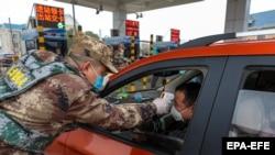 یک ارتشی در حال معاینه راننده یک خودرو به هنگام ورود به شهر ووهان.