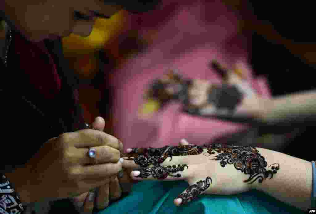 A beautician applies traditional henna designs to the hand of a customer ahead of the Muslim festivities of Eid al-Fitr in Karachi, Pakistan. (AFP/Asif Hassan)