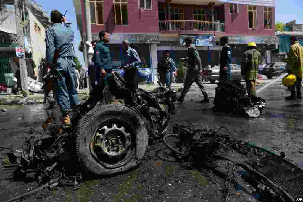 Afghan policemen inspect the aftermath of a suicide car bomb in Kabul on May 16. (AFP/Massoud Hossaini)