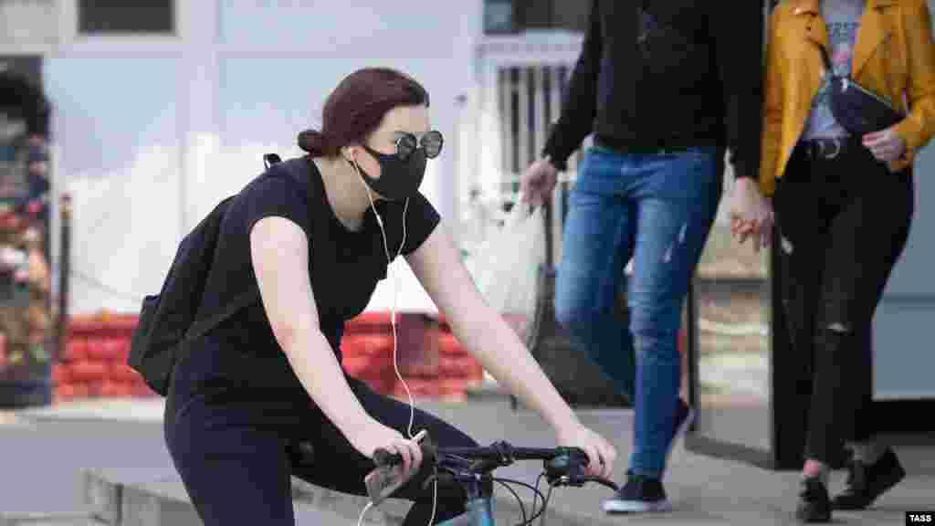 Женщина в защитной маске направляется к супермаркету на улице Кирова, Симферополь