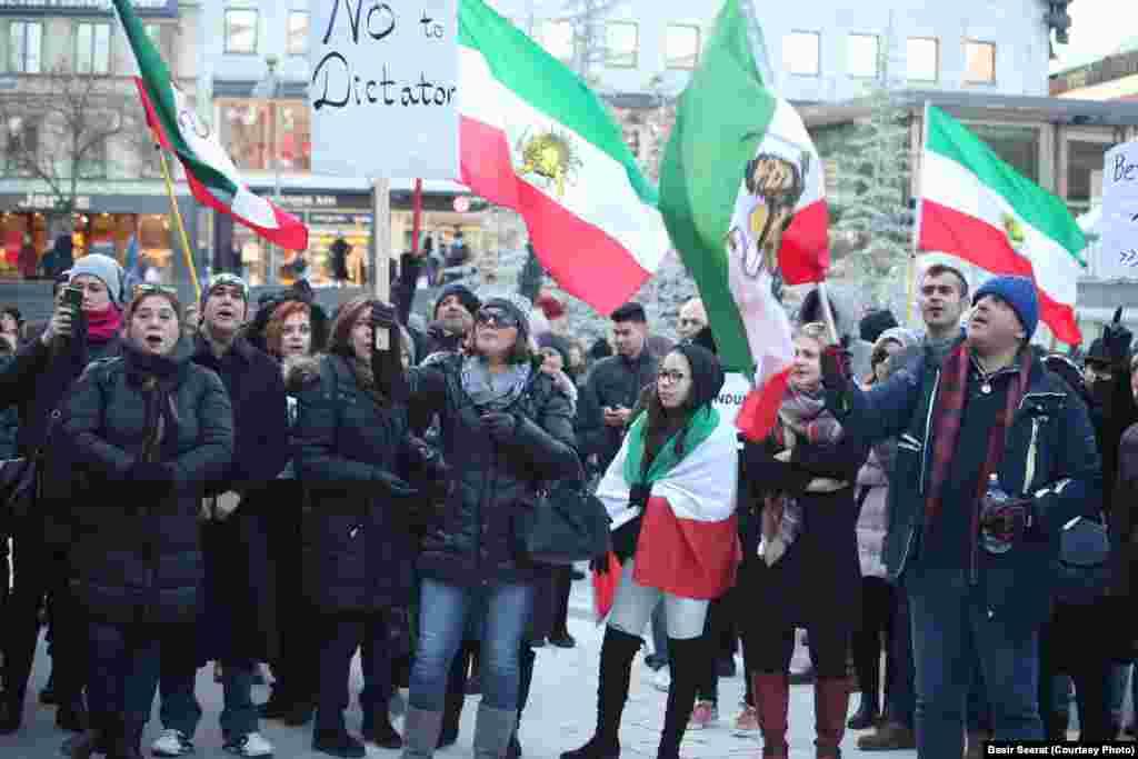 Флаги времен правления шаха в Иране в руках у протестующих в Стокгольме.