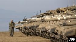 Израилдик жоокер Сирияга чек аралаш жана аннексияланган Голлан дөңсөөсүндөгү окуу базасындагы танктарды күзөтүүдө. 28-август 2013