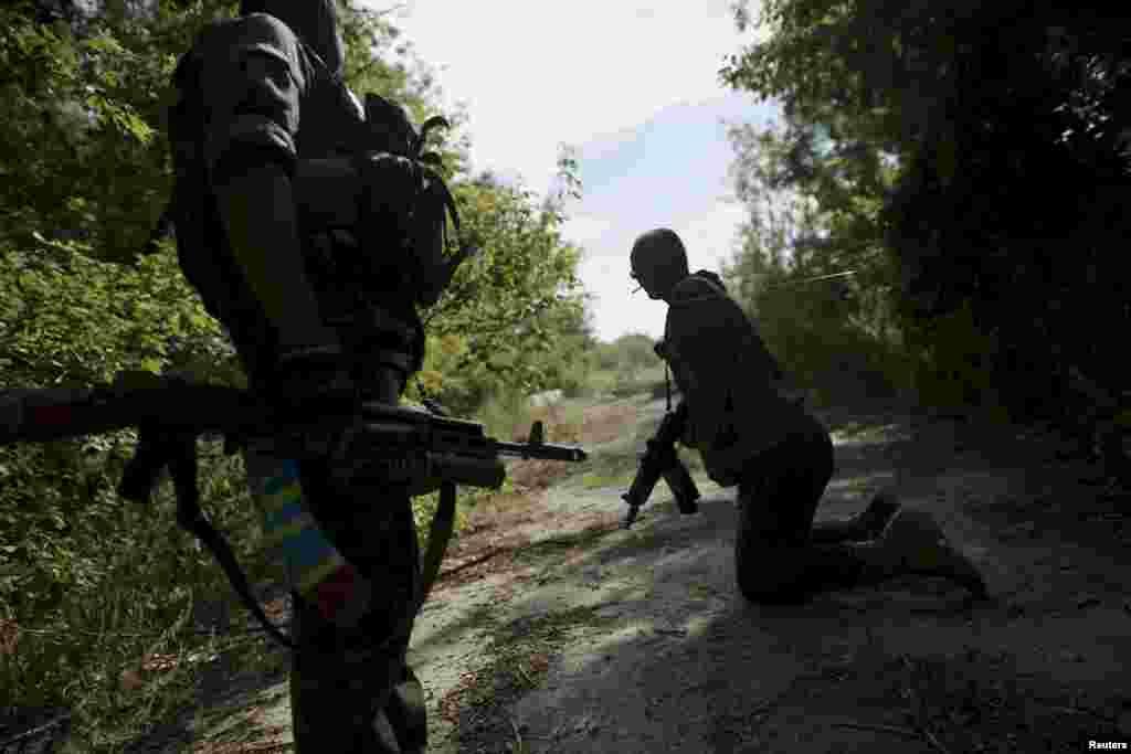 Українські військові пролазять під розтяжкою під час патрулюювання території біля села Попасна, Луганської області, 27 серпня 2015 року