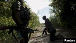 Українські військові пролазять під розтяжкою під час патрулювання території біля села Попасна Луганської області, серпень 2015 року