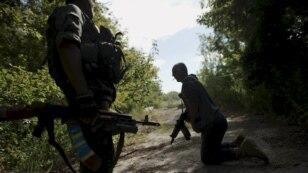 Українські військові пролазять під розтяжкою під час патрулюювання території біля села Попасна, Луганської області