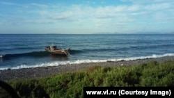 "A fishing boat rolling in the waves after it drifted to shore near the town of <a href=""https://www.google.com/maps/place/Zarubino,+Primorsky+Krai,+Russia,+692725/@42.6606725,131.0952789,471m/data=!3m1!1e3!4m5!3m4!1s0x5fb44b3e34a489a7:0x56e0e6927d0442eb!8m2!3d42.647737!4d131.0770297"" target=""_blank"">Zarubino</a> on August 30."