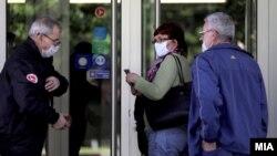 Илустрација - Луѓе со заштитни маски пред банка во Скопје