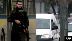 Мелвид Јасаревиќ со автоматска пушка марка АК-47 фотографиран во близина на американската амбасада