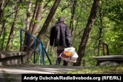 Безхатченко з пакетами прямує з території «Павлівської» лікарні у Кирилівській гай