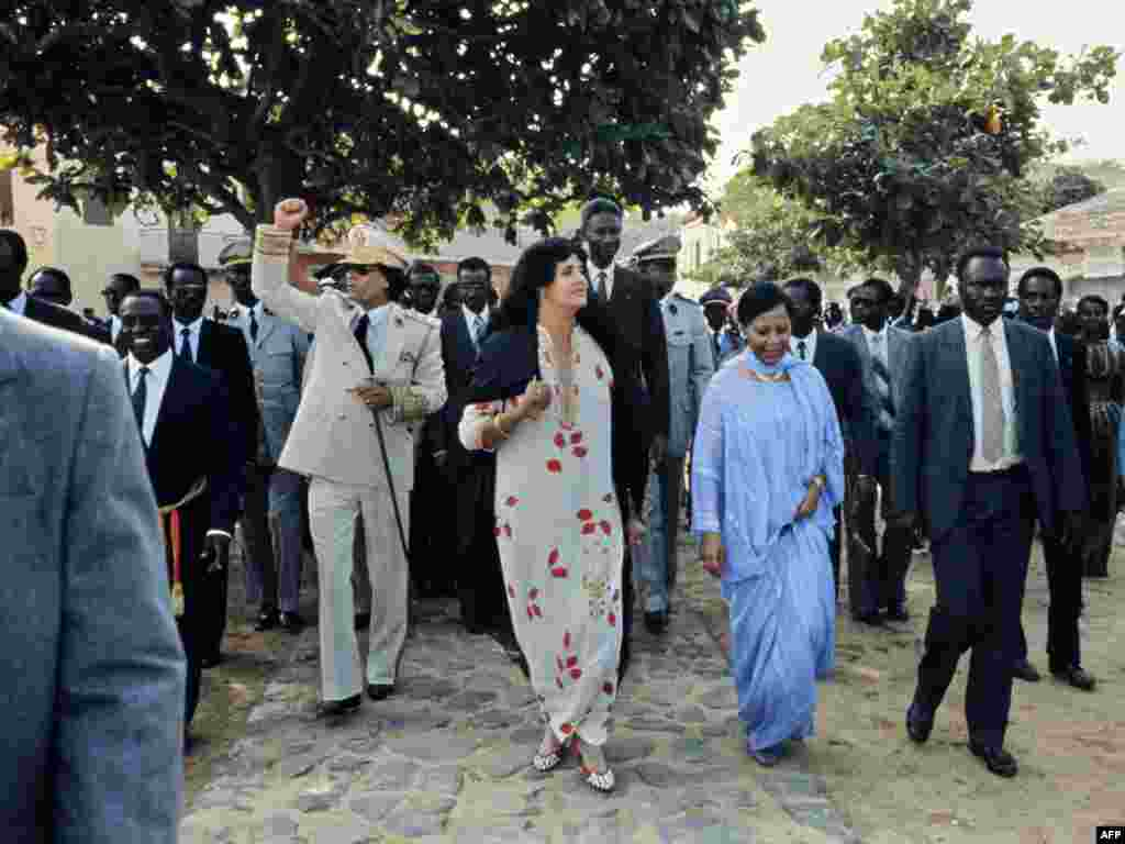 Qaddafi and his wife, Suffiya (in floral print dress), wave to the crowd upon their arrival for an official visit to Senegal in December 1985.