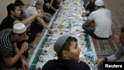 Russia - Migrant workers sit for a meal after prayers on the first day of Ramadan in a mosque in Moscow,01Apr2011