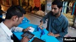 Сим-картаны каттоодон өткөрүү. Карачи, Пакистан. 3-март, 2015-жыл.
