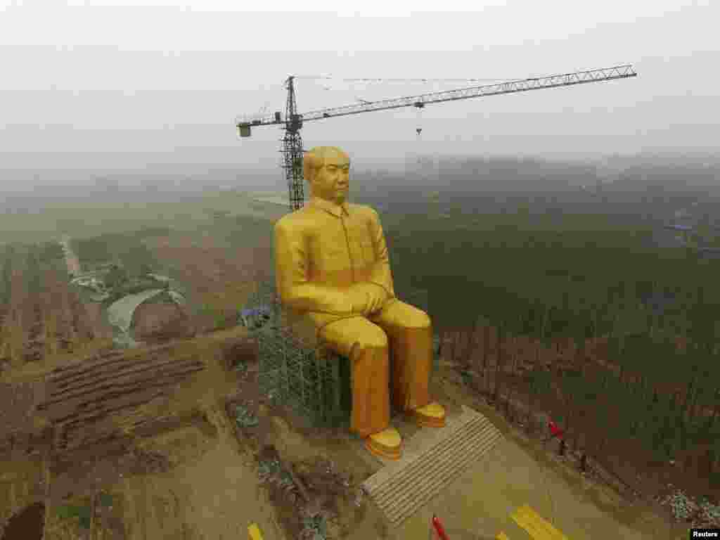 A crane is seen next to a giant statue of late Chinese leader Mao Zedong under construction near crop fields in a village of Tongxu county, Henan Province, on January 4. State media reports now say that the statue has been demolished, apparently because it lacked government approval. (Reuters)