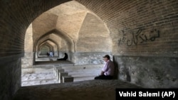 In this Tuesday, July 10, 2018 photo, people rest under an arch of the 400-year-old Si-o-seh Pol bridge, named for its 33 arches, that now spans a dried up Zayandeh Roud river, in Isfahan, Iran.