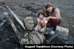 The wife and daughter of photographer Andrei Parfyonov pose with fragments of the Stalin statue.