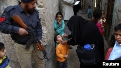 A member of the Pakistani security services escorts health workers as they administer polio vaccines to children, in Karachi, Pakistan, in January.