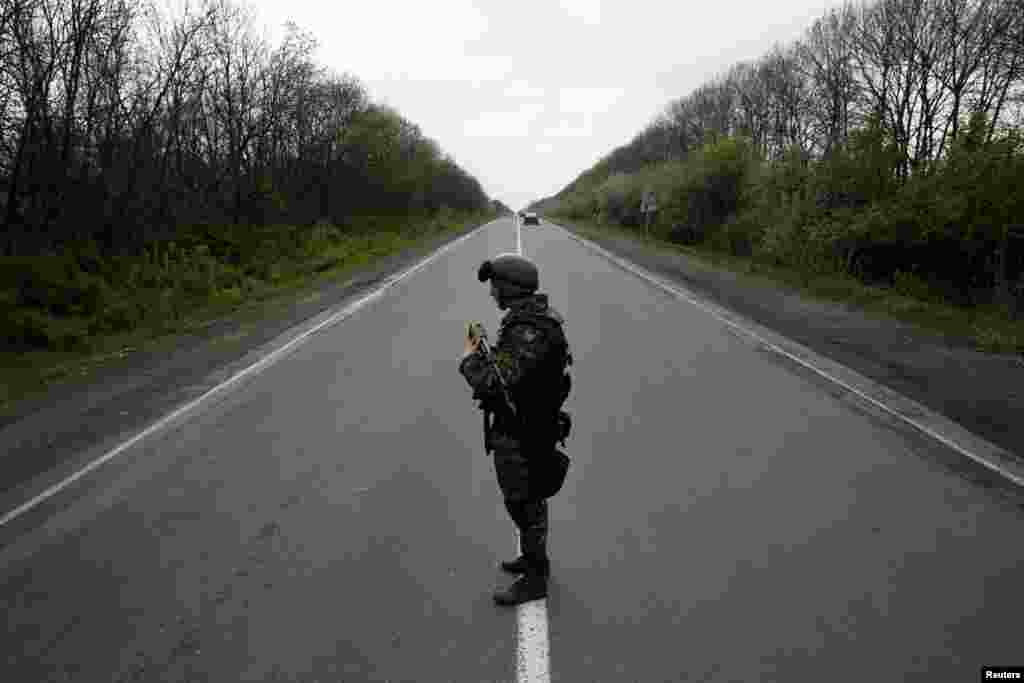 A Ukrainian soldier stands guard on a road at a checkpoint near the village of Malinivka, southeast of Slovyansk, on April 29. (Reuters/Baz Ratner)