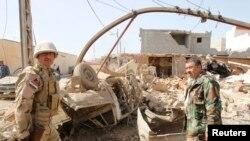 Ирактык аскерлер жанкечти жардырган автомобилдин жанында турушат. Киркуктун батыш ныптасындагы Дебис шаарчасы. 11-март, 2013