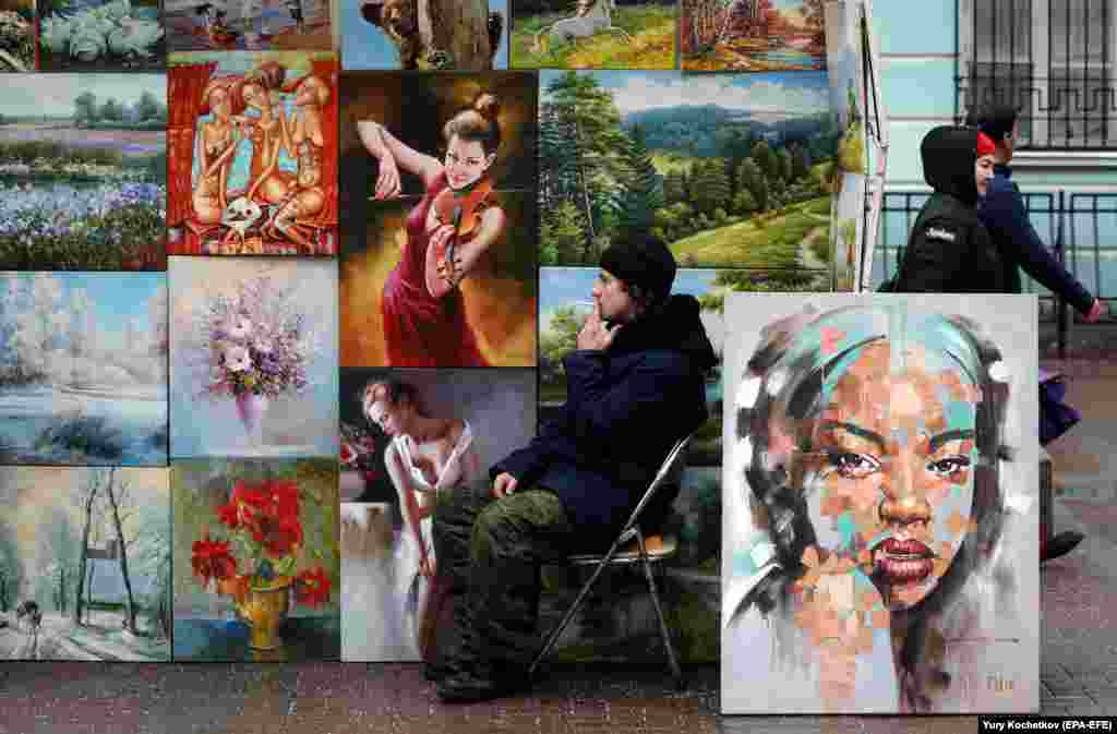 A seller of paintings smokes next to his wares on Arbat Street in central Moscow. (epa-EFE/Yuri Kochetkov)