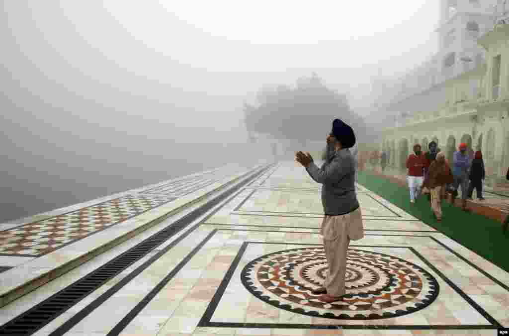A Sikh man prays at the Golden Temple, the holiest of Sikh shrines, on a dense foggy morning in Amritsar, India. (epa/Raminder Pal Singh)