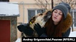 Айгуль со стерилизованной и привитой собакой, в ухе которой можно заметить жёлтую клипсу.