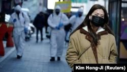 Маска таққан қыз арнайы киімдегі адамдар дезинфекция жасап жүрген көшеден өтіп барады. Сеул, Оңтүстік Корея, 5 наурыз 2020 жыл.
