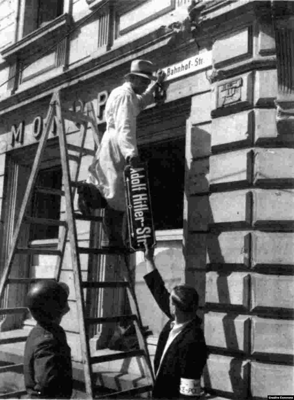 """Работници премахват табелите на бившата улица """"Адолф Хитлер"""" в Триер, Германия, през 1945 г. след капитулацията на нацистка Германия."""