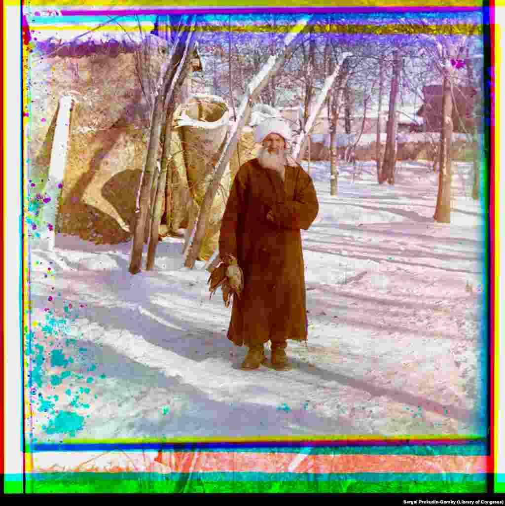 Stariji muškarac - obučen kao etnički Tadžik - drži pticu u Samarkandu.