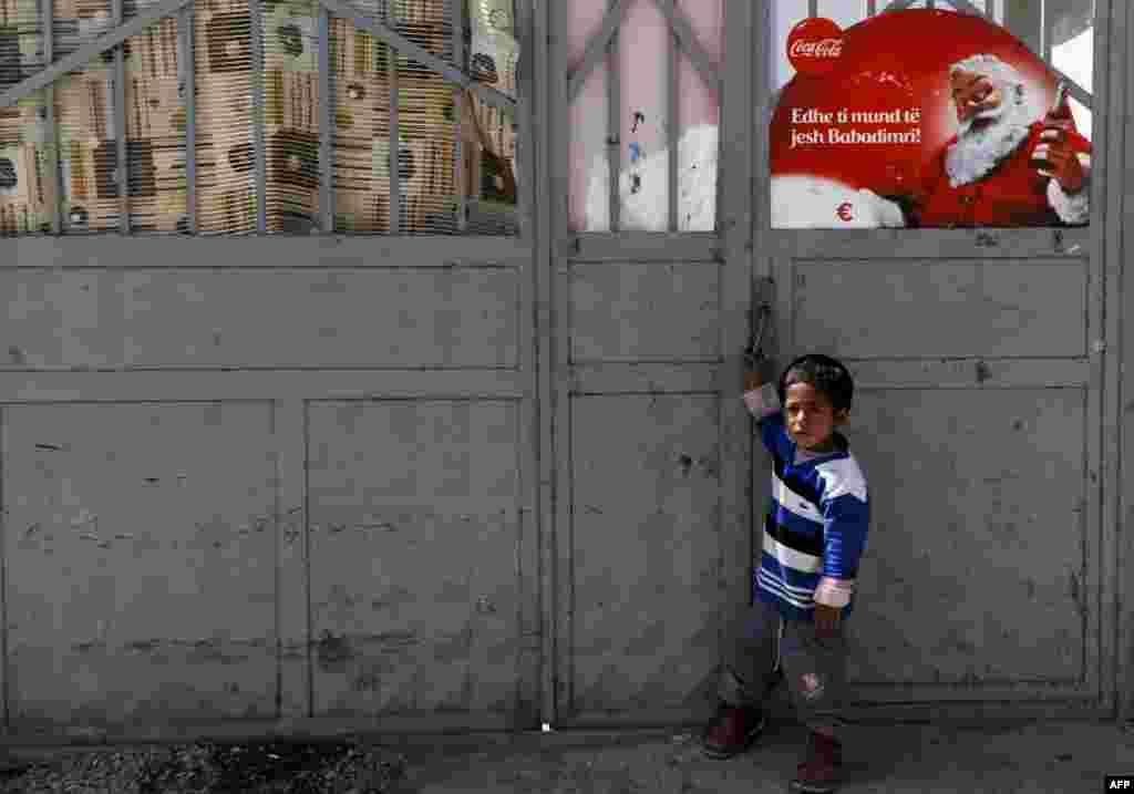 Цыганский ребенок у входа в приют в городе Гякова в Косово