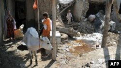 Afghanistan -- Afghan residents stand in the compound of their flood-damaged home after the waters receded in Surobi district of Kabul province on August 7, 2013.