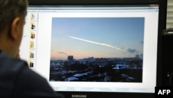 A man in Moscow looks at a computer screen displaying a picture reportedly taken in the Urals city of Chelyabinsk, showing the trail of a falling object above a residential area of the city.