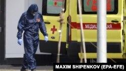Медик в защитном костюме рядом с машиной скорой помощи на территории больницы для пациентов с коронавирусом в Подмосковье.