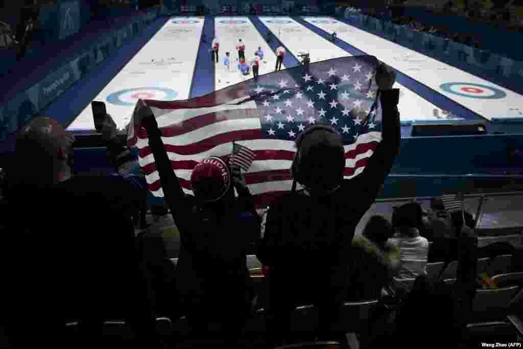 Керлінг: уболівальники розмахують американським прапором після того, як команда США виграла коло змагань з керлінгу між США та Канадою
