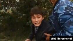 Полицейский уводит 11-летнего Нурыма Карибаева с места сноса дома в Астане. 15 августа 2014 года.