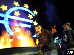 Masked protesters warm themselves at a fire after setting up camp in front of the European Central Bank in Frankfurt.